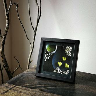 Kunstdruck einer gerahmten Fotografie zeigt eine Schale Matcha mit Matchapralinen