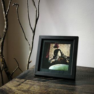 Kunstdruck einer gerahmten Fotografie zeigt eine dunkle Teeschale mit Matcha und einem Bild von Tomoe Gozen.