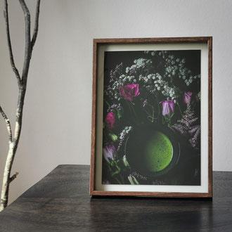 Kunstdruck einer gerahmten Fotografie zeigt eine Teeschale mit Matcha im Blumenarrangement