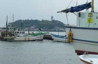 鎌倉市・腰越漁港の漁船と江ノ島遠望