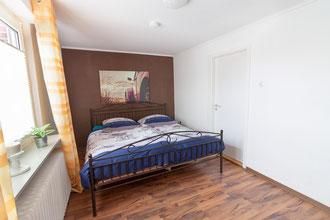 Schlafzimmer mit bezogenem Bett
