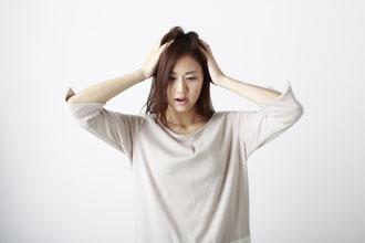 頭を抱えている女性の画像