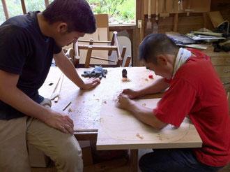 削るヨネトさん(右)、見入るカワグチさん(左)