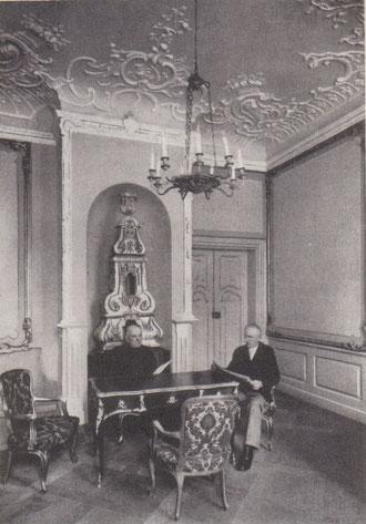Zwei Rentner in den 1950er Jahren am Tisch in barocken Mirower Schloss sitzend.