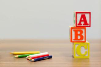 Foto: Buchstaben-Bauklötze und Buntstifte auf einem Tisch