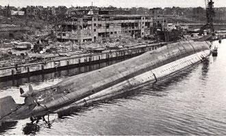 """Die gekenterte (nach Bombenangriff April 1945) """"Admiral Scherr"""" im Ausrüstungsbecken (Foto: Imperial War Museum, London)"""