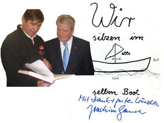 Bundespräsident Joachim Gauck und Manfred Wille betrachten bei einem Empfang im Schloss Bellevue die Dokumentation über die Paddeltour zur Deutschen Einheit