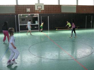 Mädchen und Jungen spielen gemeinsam Fußball