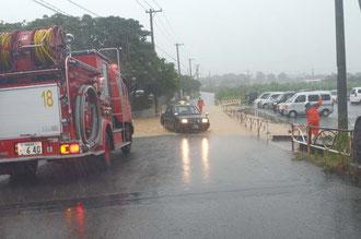八重山病院東側の市道が冠水、消防署員が排水対策に追われた=午前9時40分、大川