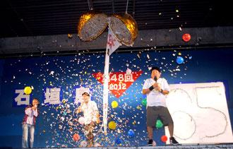 中山市長(中央)が市制施行65周年を祝うくす玉を割った。右に「65」と書かれたボードがある=4日夜、真栄里公園