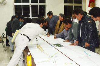 新石垣空港のアクセス道計画の図面を見る地権者ら=宮良公民館