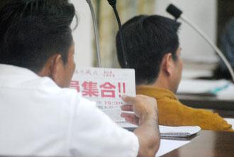 集会参加を呼び掛けるビラを手に市当局を追及する仲嶺氏(18日)