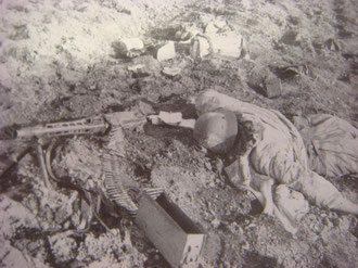 A dead German Grenadier lies behind his MG42