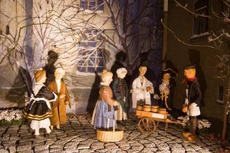 Hillige Magd, Frau Müller-Hermann, die Marktfrau, die Frau aus dem Veedel (Frau Färber), der jüdische Apotheker und der Hillige Knäächt versammeln sich um den holländischen Heringsverkäufer in der Milieukrippe von Lyskirchen
