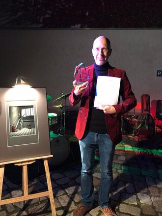Sieger im Licht: Preisträger Frank Kunert mit Zille-Skulptur und Urkunde im Radeburger Museumshof         Foto: Galerie Komische Meister