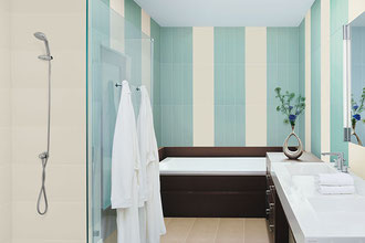 A bathroom a tub, shower, and vanity. The vanity has a solid white top on dark wood. The soaking tub has a dark brown surround. The walls have sky blue and cream tiles set in vertical stripes.