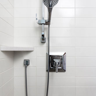 A shower with white, matte-finish subway tiles set in a stacked pattern. There is a white quartz corner shelf and chrome shower head.