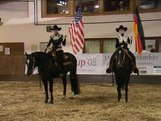 Den schwierigen Anfang unserer Show übernahmen Jasmin und Theresa, die in tollen, glitzernden Western-Outfits und riesigen Fahnen auf ihren Pferden einritten. Schlagartig funkelte ein Blitzlicht-Gewitter durch die abgedunkelte Halle.