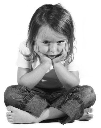 Ein Kind sitzt traurig auf dem Boden, den Kopf auf die Hände gestützt und schaut in die Kamera.