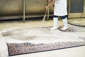 Teppichwäsche einzeln, flachliegend mit Seife und Wasser.