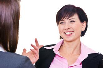 Eine Frau mit strahlendem Lachen, die von einer ihr gegenübersitzenden Frau etwas gesagt bekommt.