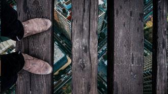 Die Unterschenkel und Schuhe eines Mannes, der auf einer sehr hohen Holzbrücke steht, deren Bretter so weit auseinander stehen, dass man die Hochhäuser der Stadt darunter sehen kann.