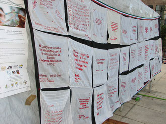 死者を悼む赤い文字が縫い取られたハンカチがはためく