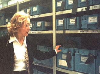 Helga Karl steht vor dem Lager-Regal mit Kleinteilen in der Montage