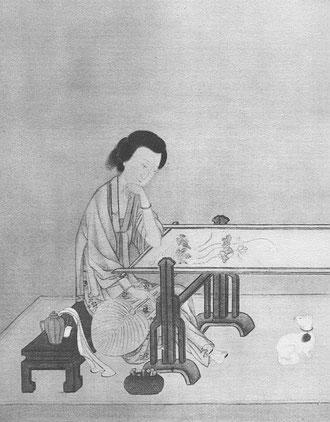 Une jeune femme qui brode des fleurs brillantes sur une étoffe de soie.