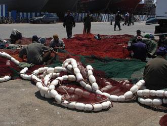 Pêcheurs marocains à Essaouira reprisant les filets de pêche