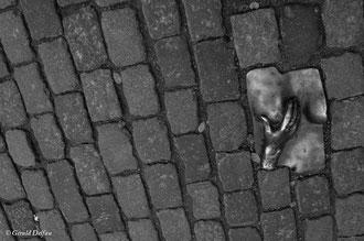 Main sur un sein en bronze incrusté dans les pavés d'une rue d'Amsterdam