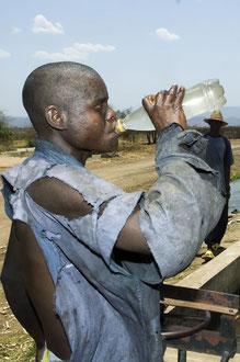 Saisonarbeiter aus Mosambik ernten Zuckerrohr unter Sklavenähnlichen Bedingungen im Süden Malawis. Sie nutzen das Wasser aus den Bewässerungsgräben als Trinkwasser, was zu Infektionen und Durchfällen führt. / Zucker - Malawi