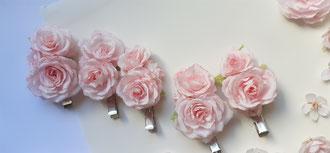 Pince cheveux ornées de petites roses de papier.