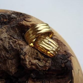 Eheringe in Gelbgold 750 mit grober Wellenstruktur und 3 weissen Brillanten, Damenring CHF 1600.-, Herrenring CHF 1450.-