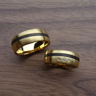 Eheringe in Gelbgold 750 matt, mit eingelegter Carbon-Linie und 3 weissen Brillanten, Damenring CHF 1400.-, Herrenring CHF 1400.-