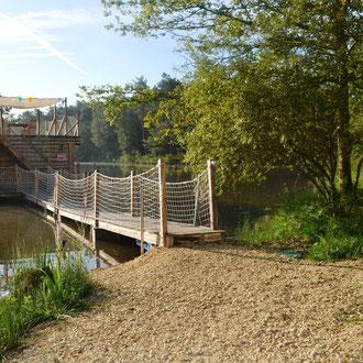 Un accès de la berge à la cabane flottante par une passerelle en bois