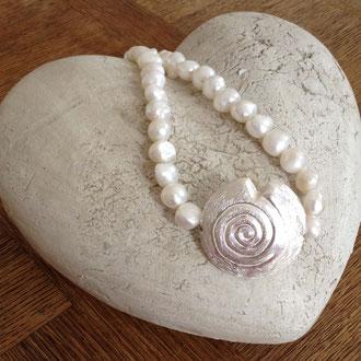Diese wunderschöne Kette besteht aus Muschelkern-Perlen und einer aus Kupfer versilberten Muschel.
