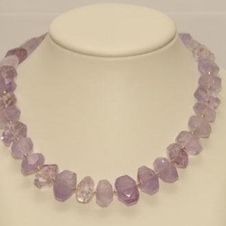 Diese violette Kette aus Ametrinen und kleinen Zwischenteilen aus Silber besticht durch ihre Farbe und durch die Unregelmäßigkeit der einzelnen Perlen. Der Verschluß ist von Hand gemacht und aus Silber. Länge 50,5 cm.