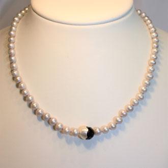 Graue Süßwasser-Zuchtperlenkette, einzeln abgeknotet, mit einer Onyxkugel, die frech unter einer Silber-Halbschale hervorlugt. Länge 44 cm