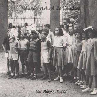 1950 Chorale pour la fête des mères sous le préau (cour école des garçons)