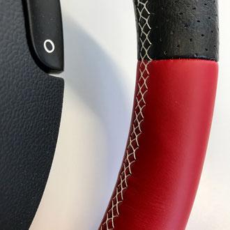 Détail volant Renault Clio 3 RS en cuir nappa lisse rouge, cuir perforé noir, couture blanche, point tissé