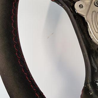 Détail volant Audi TT en Alcantara noir, coutures noires et rouges, point losange