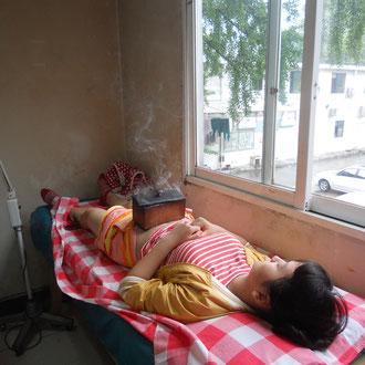 Tina während der Behandlung - sie lag mindestens eine halbe Stunde mit den Nadeln in Bauch und Beinen und diesem stinkenden Teil auf dem Bauch da. Wie tapfer!