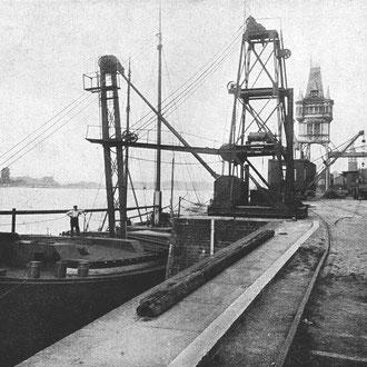 Ein Hafenkrahn und Werftgebäude.