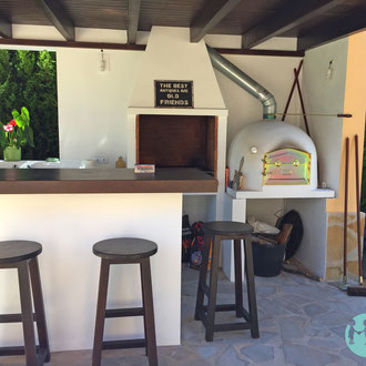 New outdoor kitchen completely with constructed barbecue, oven, bar and roof