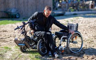 Ein Mann wechselt am Strand vom Geländerollstuhl namens Zoom  in einen gewöhnlichen Rollstuhl.