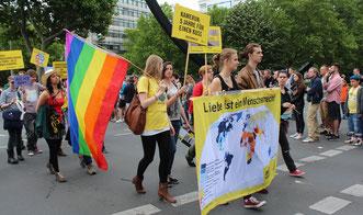 """Menschen mit Regenbogenfahne und Plakaten CSD Berlin. """"LIebe ist ein Menschenrecht"""". Foto: Helga Karl 2015"""