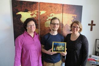 Marion Reichow (von links), Alexander Sichwardt und Tabea Kölbel mit dem Glasbild mit einem radelnden Elefanten als Dankeschön für die vorbildliche Zusammenarbeit
