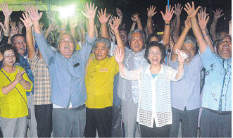 バンザイ三唱で4選の喜びを爆発させる外間氏と家族、支持者ら=6日夜、選対本部前