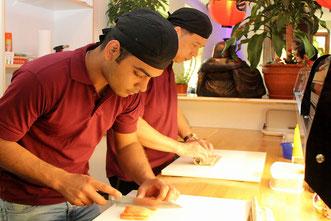 Sushi-Koch bei der Zubereitung aus frischen Zutaten